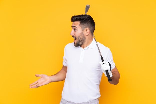 Uomo del giocatore di giocatore di golf sopra la parete gialla isolata con espressione facciale di sorpresa