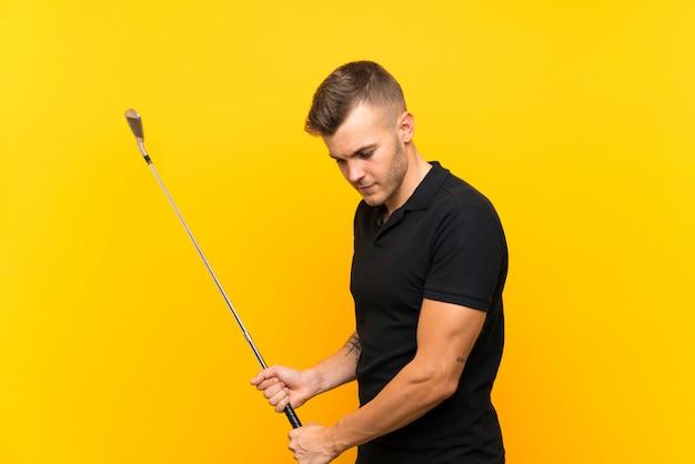 Uomo del giocatore di giocatore di golf sopra la parete gialla isolata