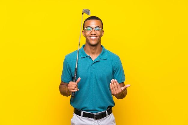 Uomo del giocatore di golf americano africano che invita a venire con la mano. felice che tu sia venuto