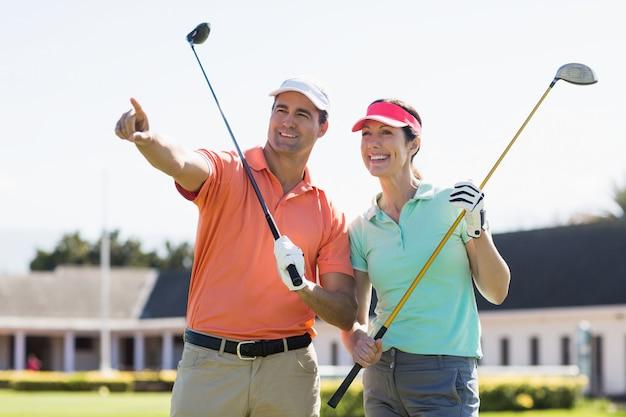 Uomo del giocatore di golf che indica mentre facendo una pausa donna