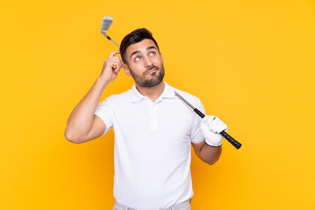 Uomo del giocatore di golf sulla parete gialla isolata che ha dubbi e con espressione del viso confuso
