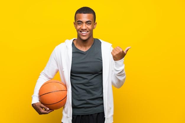Uomo del giocatore di pallacanestro afroamericano che indica il lato per presentare un prodotto