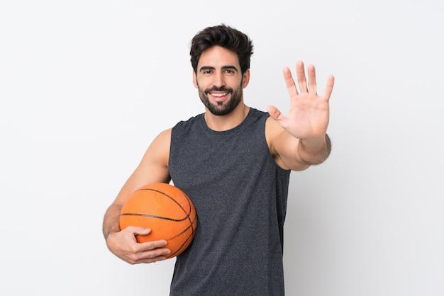 Uomo del giocatore di pallacanestro con la barba sopra la parete bianca isolata che saluta con la mano con l'espressione felice