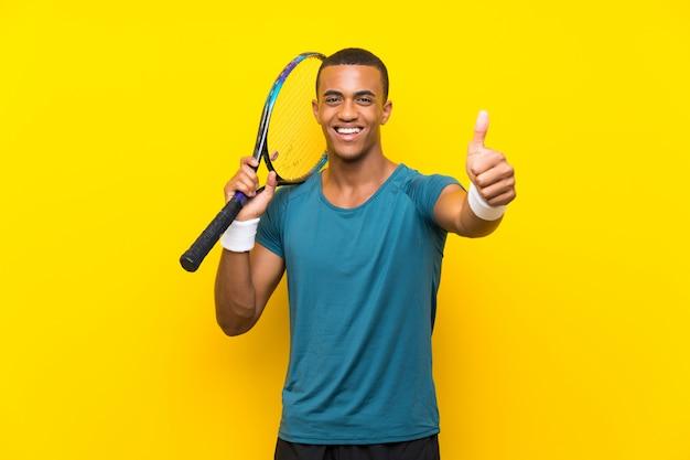 Uomo del giocatore di tennis afroamericano con i pollici in su perché è successo qualcosa di buono