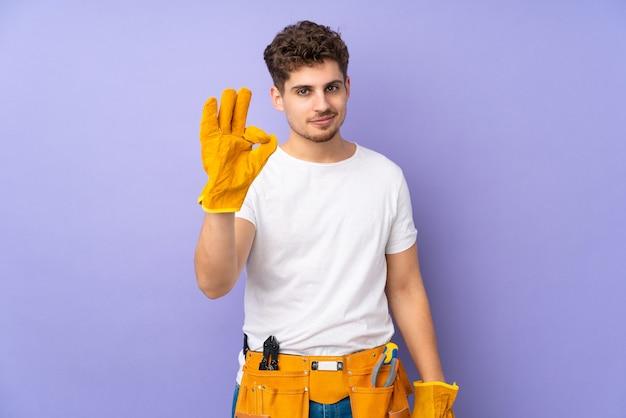Uomo del giovane elettricista sopra isolato sulla porpora che mostra un segno giusto con le dita