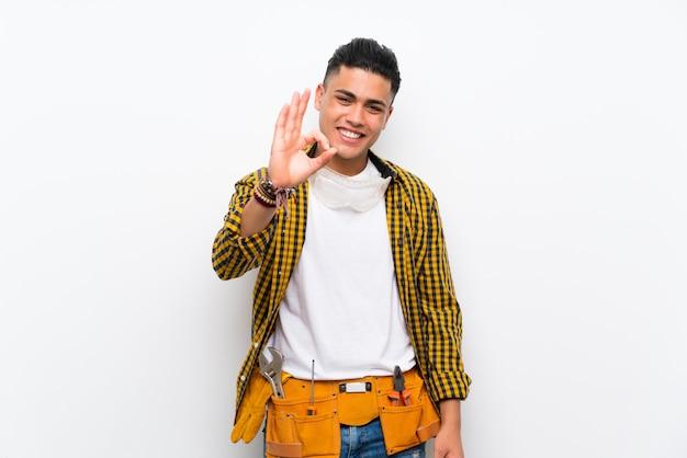 Uomo del giovane elettricista sopra la parete bianca isolata che mostra segno giusto con le dita
