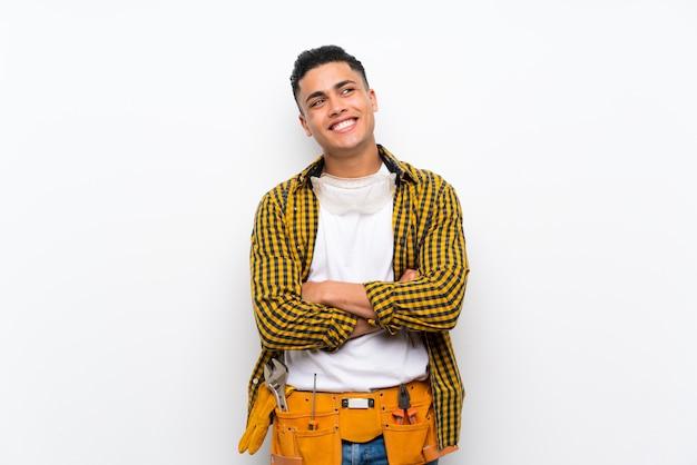 Uomo del giovane elettricista sopra la parete bianca isolata che osserva in su mentre sorridendo