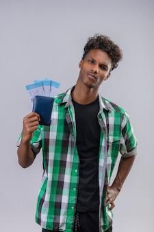 Uomo del giovane viaggiatore afroamericano che tiene i biglietti aerei sorridente fiducioso positivo e felice soddisfatto in piedi su sfondo bianco