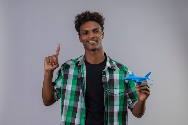 Uomo del giovane viaggiatore afroamericano che tiene l'aeroplano del giocattolo che indica il dito in su che sorride con l'espressione sicura sul fronte che sta sopra fondo bianco