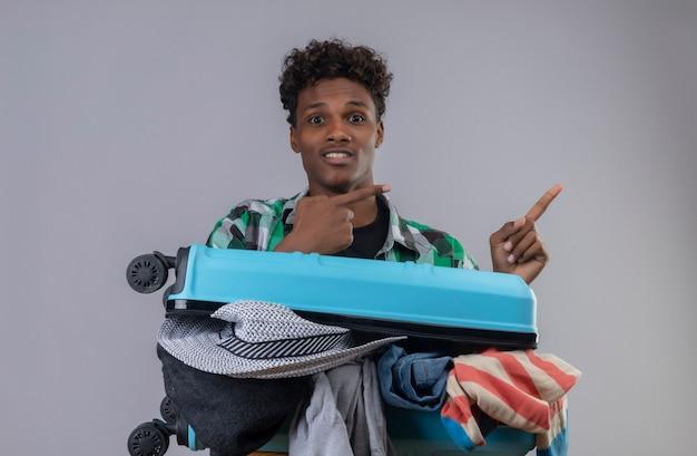 Uomo del giovane viaggiatore afroamericano con la valigia piena di vestiti che guarda l'obbiettivo felice e sorpreso che punta con le dita a lato in piedi su sfondo bianco