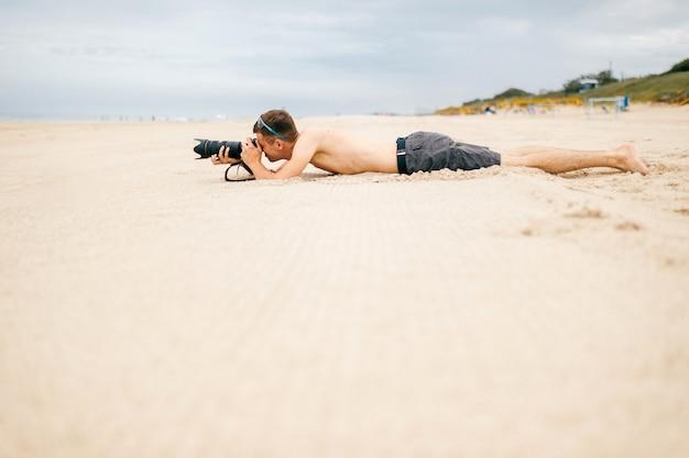 Uomo del giovane viaggiatore che si trova sulla spiaggia vicino al mare in vacanza e che fa le foto della natura. uomo scalzo bello in topless con fotocamera e grande lente spiare le persone da lontano. tempo per hobby. ragazzo che riposa sulla sabbia