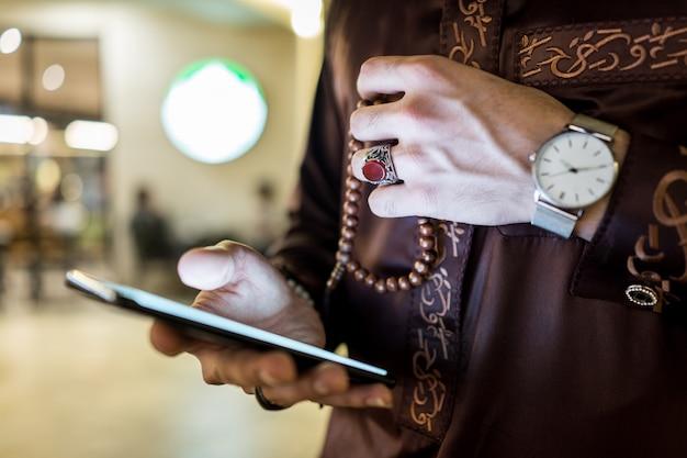 Uomo del golfo con il primo piano disponibile dello smart phone