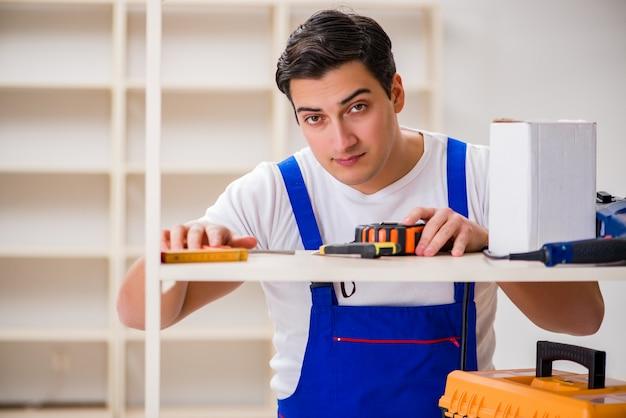 Uomo del lavoratore che ripara lo scaffale per libri di montaggio