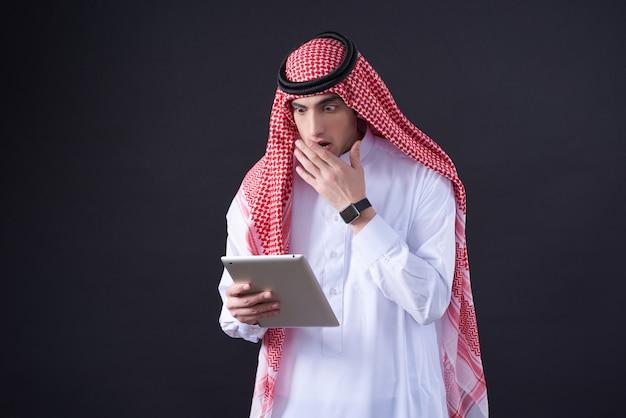 Uomo del medio-oriente che posa facendo uso della compressa isolata.