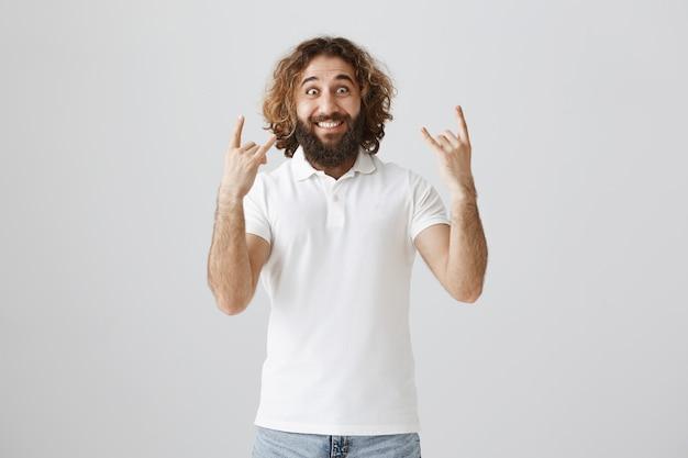 Uomo del medio oriente emozionante e felice che mostra il gesto del rock-n-roll, divertendosi
