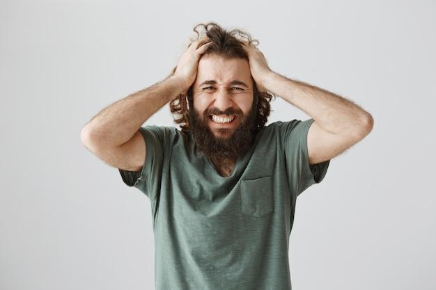 Uomo del medio oriente frustrato e sconvolto che fa smorfie, afferra la testa angosciata