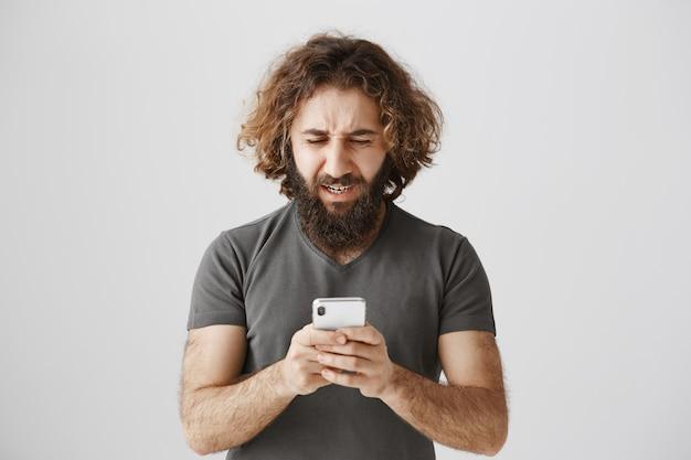 Uomo del medio oriente frustrato e sconvolto che guarda il telefono in difficoltà