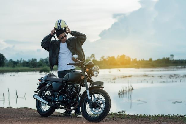Uomo del motociclista con la sua moto accanto al lago naturale e bello.