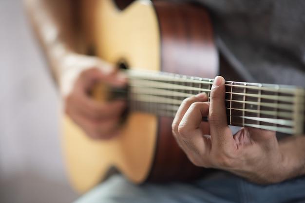 Uomo del musicista che gioca chitarra acustica