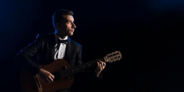 Uomo del musicista con farfallino, suonare la chitarra classica