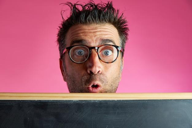 Uomo del nerd pazzo dietro il gesto divertente della lavagna