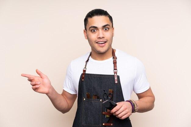 Uomo del parrucchiere in un grembiule sul beige sorpreso e puntando il dito verso il lato