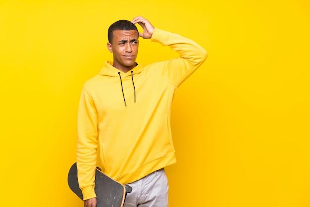 Uomo del pattinatore afroamericano che ha dubbi e con espressione del viso confuso