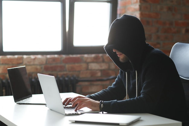 Uomo del pirata informatico sul computer portatile