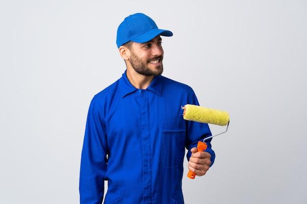Uomo del pittore che giudica un rullo di pittura isolato su bianco che guarda al lato e sorridere