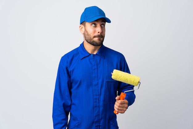 Uomo del pittore che giudica un rullo di pittura isolato su bianco che ha dubbi mentre cerca