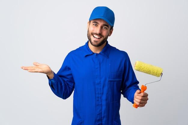 Uomo del pittore che giudica un rullo di pittura isolato sul copyspace bianco della tenuta della parete immaginario sulla palma per inserire un annuncio