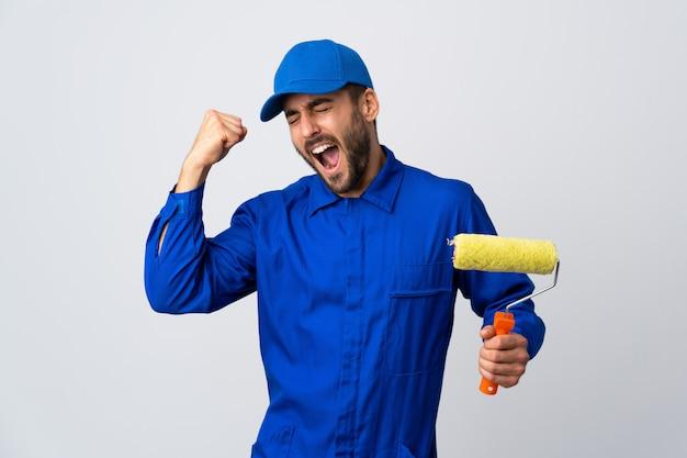 Uomo del pittore che giudica un rullo di pittura isolato sulla parete bianca che celebra una vittoria