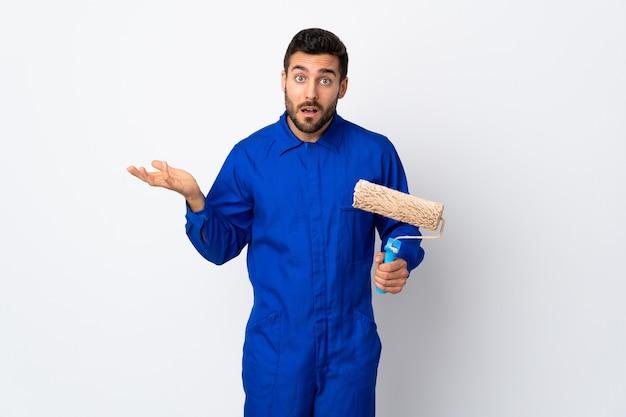 Uomo del pittore che giudica un rullo di pittura isolato sulla parete bianca che fa gesto di dubbi