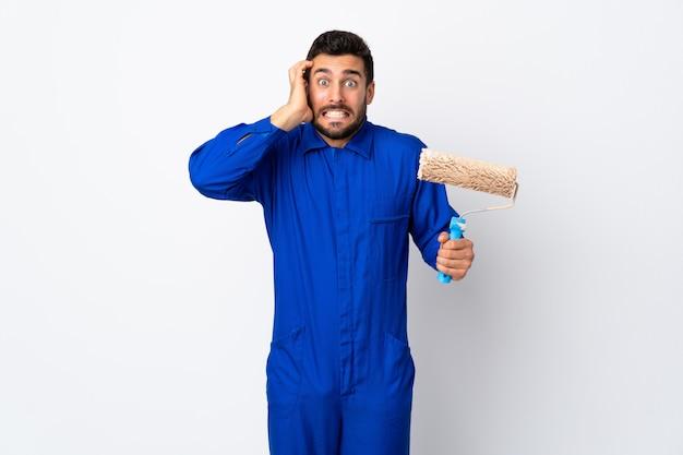 Uomo del pittore che giudica un rullo di pittura isolato sulla parete bianca che fa gesto nervoso