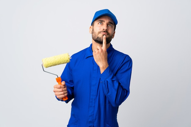 Uomo del pittore che giudica un rullo di pittura isolato sulla parete bianca che ha dubbi mentre cercava