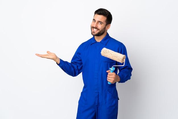 Uomo del pittore che tiene un rullo di vernice isolato su bianco che estende le mani a lato per invitare a venire