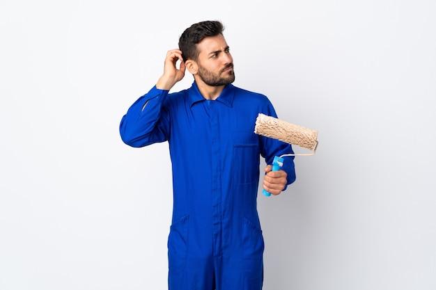 Uomo del pittore che tiene un rullo di vernice isolato su bianco che ha dubbi mentre si gratta la testa