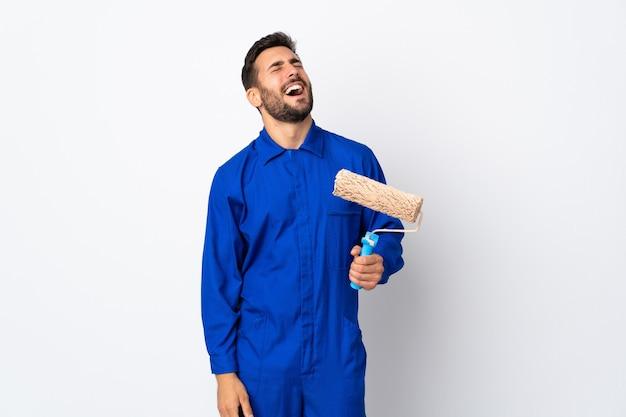 Uomo del pittore che tiene un rullo di vernice isolato sulla risata bianca