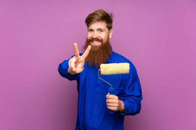 Uomo del pittore con la barba lunga sopra fondo porpora isolato che sorride e che mostra il segno di vittoria
