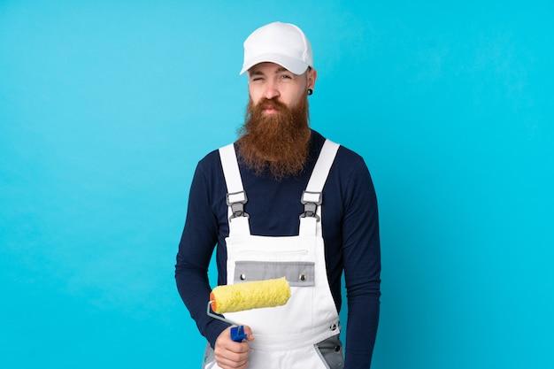 Uomo del pittore con la barba lunga sopra la parete blu isolata triste