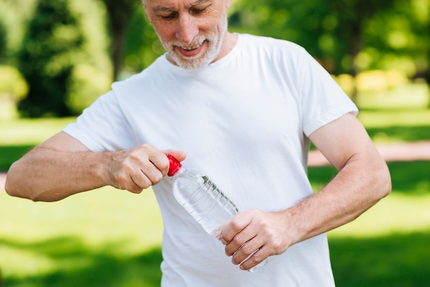 Uomo del primo piano che apre una bottiglia di acqua