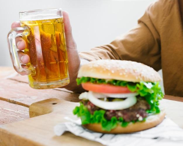 Uomo del primo piano che beve birra e che mangia hamburger
