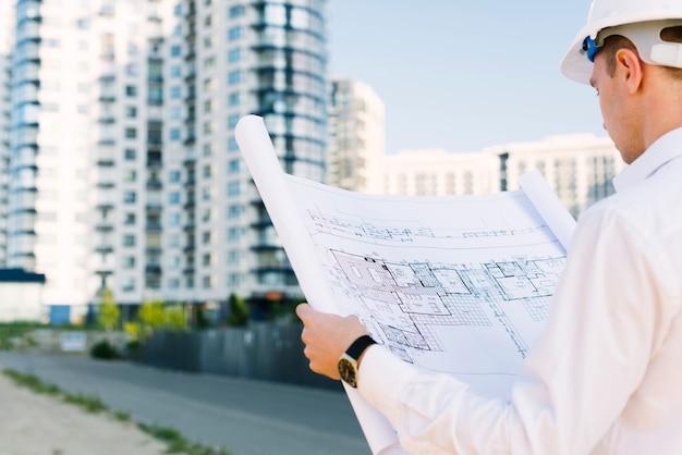 Uomo del primo piano che esamina progettazione di edifici