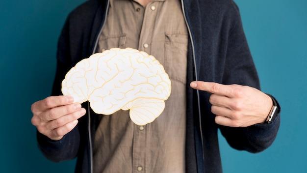 Uomo del primo piano che indica al cervello di carta