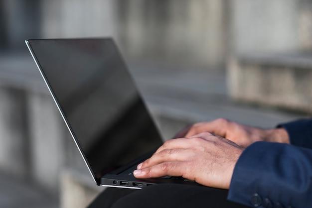 Uomo del primo piano che lavora al computer portatile