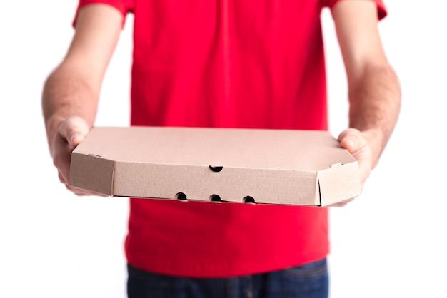 Uomo del primo piano che mostra il contenitore di pizza