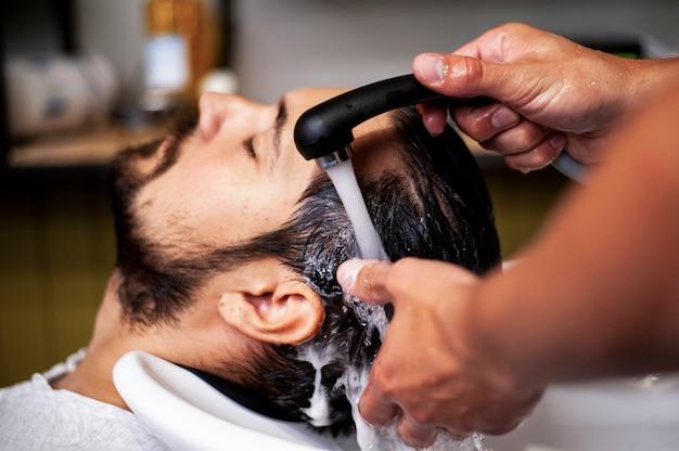 Uomo del primo piano che ottiene un lavaggio dei capelli