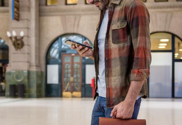Uomo del primo piano che per mezzo dello smartphone