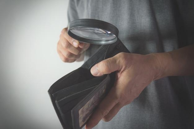 Uomo del primo piano che sta e che tiene lente d'ingrandimento per lo sguardo nel portafoglio