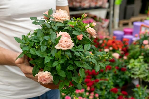Uomo del primo piano che tiene i fiori eleganti